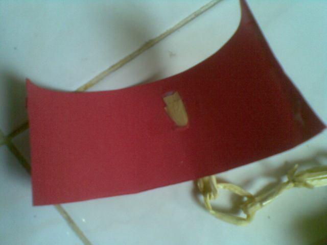 lubangi bagian belakang karton untuk mengesolasi tali rafia di balik karton. Bagian tepi karton beri esolasi bolak balik untuk membuka dan menutup borgol dari tangan anak.
