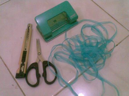 siapkan cutter, pita berbagai warna, gunting dan alat pelubang kertas