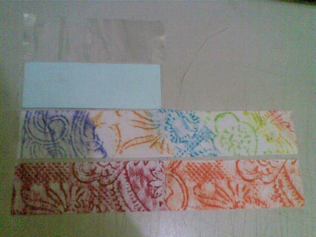 potong kertas tebal seukuran plastik es lilin penuh (kurangi sekian mili agar tidak sempit saat dimasukkan), potong kertas 'batik' dalam dua kali ukuran plastik es lilin. Setelah itu lipat kertas 'batik' menjadi dua, sematkan kertas tebal di sela-sela lipatan.