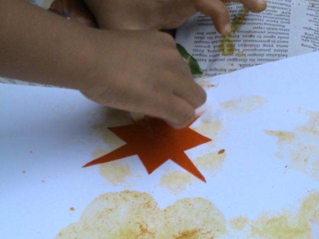 gunting kertas berbentuk bintang lalu buat cap di sekeliling menggunakan kapas celup warna , setelah kertas diangkat akan terlihat cap bintang