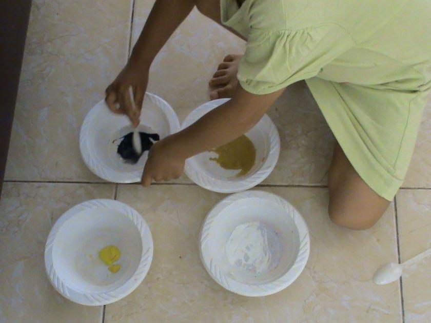 menggunakan sendok plastik untuk mencampur warna