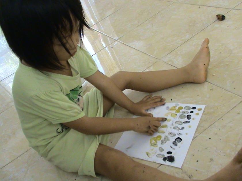 mentutul tutul dengan jari yang sudah dicelupkan ke dalam cat air